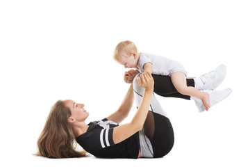 Portrait of young mother training fitness with little child isolated at white background. Concept of healthy family and sport lifestyle