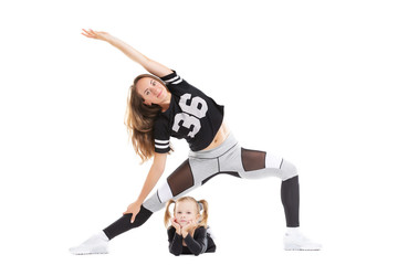 Young mother is practicing fitness with daughter isolated at white background.