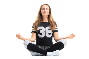 Portrait of young woman practicing yoga in lotus pose isolated at white studio background.