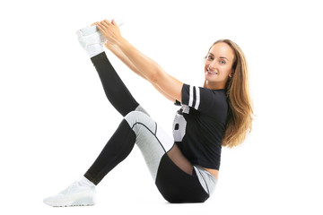 Portrait of young woman making fitness workout exercises stretching leg isolated at white background.