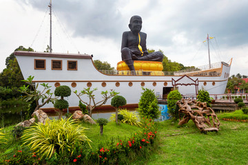 Statue of praying monk Luang Phor Thuad at Wat Bo Phuttharam, kok Samui, Thailand at picturesque green park background.