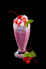 Vertical image of cherry milkshake cocktail decorated with mint isolated at black background.