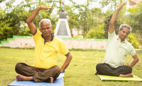 Happy senior people doing yoga by stretching hands - Concept of Senior people fitness and healthy lifestyle - two elderly man busy in morning exercise