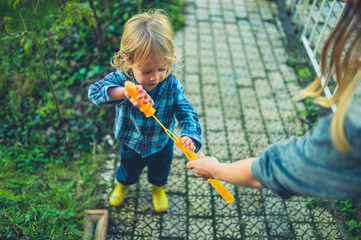 Toddler blowing bubble swith his mother in garden