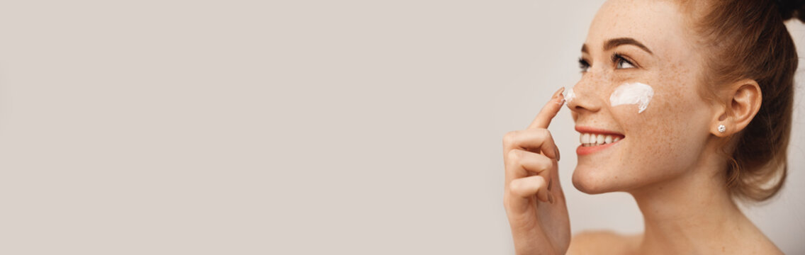 Close up side view portrait of a charming young woman with red hair and freckles applying cream on her face and nose with finger laughing isolated on white wall