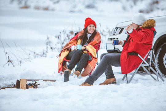 man with woman sitting on chairs near camp fire in winter time. car travel.