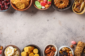 Variety of snacks and sweets on gray background. Waffles, nuts, sweets, cookies, chips and fruits, top view.