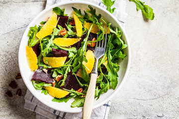 Beetroot and orange salad with arugula and nuts in white bowl, top view. Healthy vegan food concept.