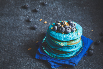 Blueberry blueberry pancakes with coconut chips on dark background.