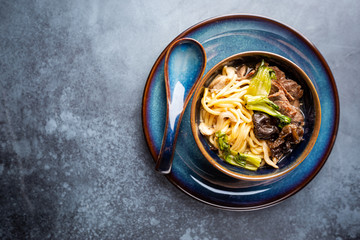 Asian ramen noodles soup with beef, oyster mushrooms and vegetables in bowl on gray background, top view
