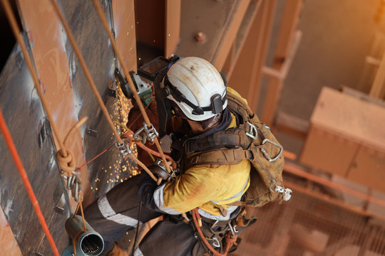 Tope view of rope access technician welder services using power grinder working at height hanging on rope wearing white helmet head fall protection while grinding construction site Sydney, Australia
