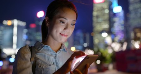 Wall Mural - Woman use of smart phone in city at night