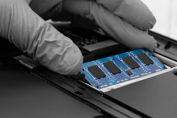 Technician installing RAM into the memory slot on a laptop computer.  Abstract image with selective colour