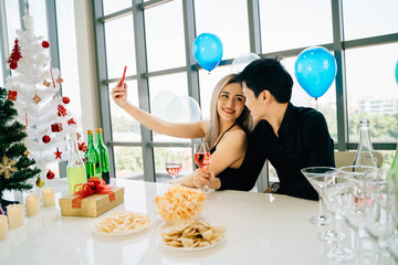 Young adult Asian couple celebrates dinner together while taking a selfie photo with smart phone in Christmas winter party