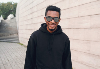 Wall Mural - Portrait happy young smiling african man wearing black hoodie, sunglasses on city street