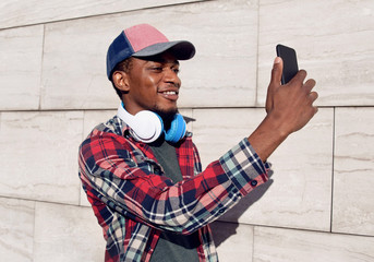 Modern smiling african man taking selfie picture by phone with headphones wearing baseball cap, plaid shirt on city street