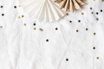 Christmas, New Year composition. Decorative paper stars, golden and black confetti on white linen...