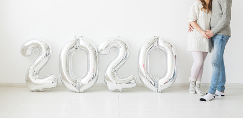 Holidays, festive and party concept - Happy loving couple near silver 2020 balloons on white...
