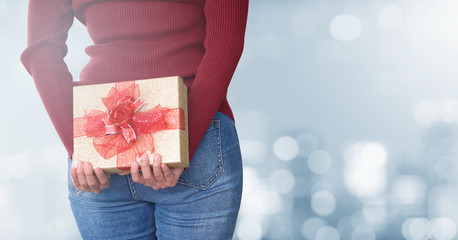 Woman holding gift box behind, with Bokeh light background