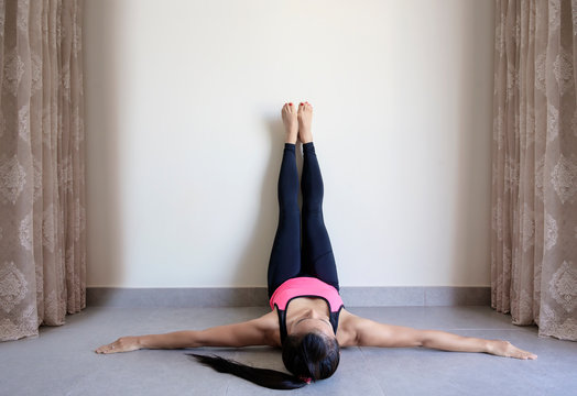 Yoga woman feet up relaxing in room on wall background