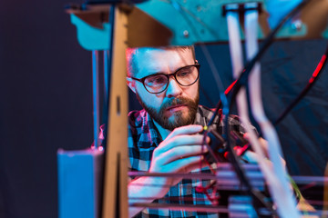 Young male designer engineer using a 3D printer in the laboratory and studying a product prototype, technology and innovation concept
