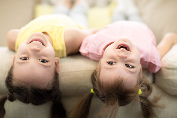 Cute kids playing and relaxing on sofa at home together