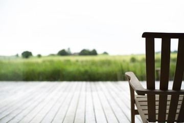 Beautiful view of a wooden chair on a porch in front of a grass covered field