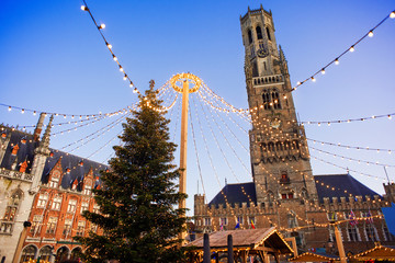 Traditional Christmas market in Europe, Bruges, Belgium. Main town square with decorated tree and lights. Christmas fair concept
