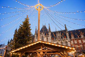 Beautiful Christmas market in Europe, Bruges, Belgium. Main town square with decorated tree and lights. Christmas fair concept