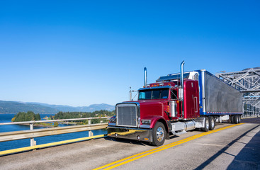 Red classic bonnet big rig semi truck transporting frozen cargo in bright refrigerated semi trailer driving on the truss bridge across the river