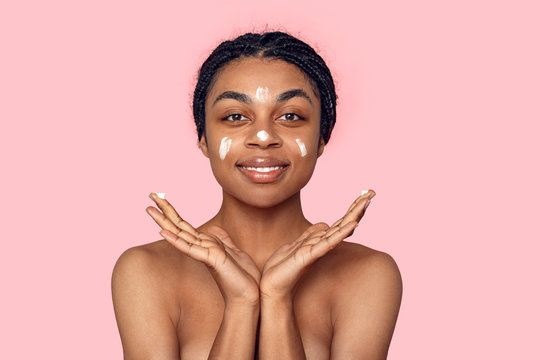 Beauty Concept. Young african woman isolated on pink having cream on face posing smiling friendly and calm