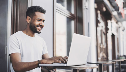 Smiling man using laptop computer in a city. Young handsome student men having coffee break. Modern lifestyle, connection, business, freelance work concept