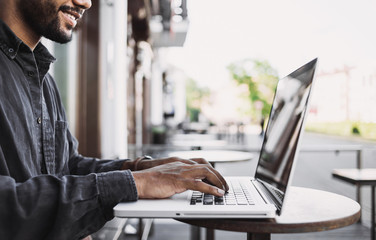 Smiling man using laptop computer in a city. Young handsome student having coffee break. Modern lifestyle, connection, business, freelance work concept