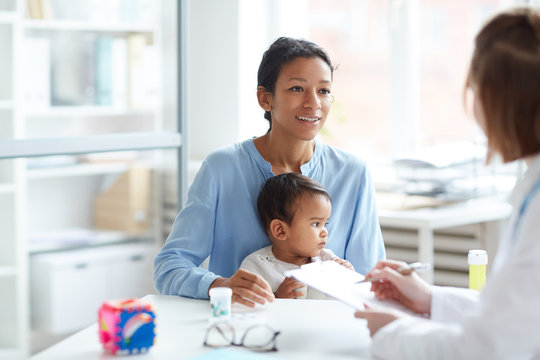 Young mother together with her baby sitting and talking to the pediatrician at doctor's office