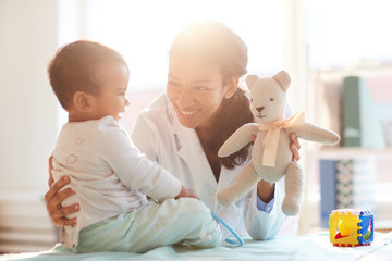 Young female doctor smiling and playing with baby boy during her visit