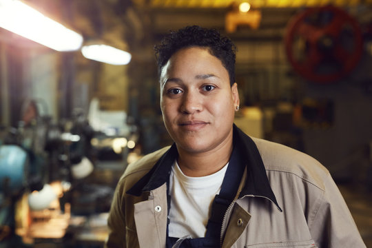 Head and shoulders portrait of contemporary mixed-race woman posing in factory workshop at looking at camera, copy space