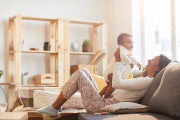 Warm toned portrait of young African-American mother playing with baby on couch lit by sunlight, copy space