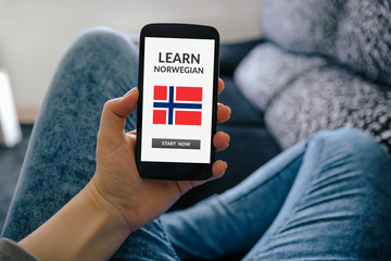 Girl holding smart phone with learn Norwegian concept on screen
