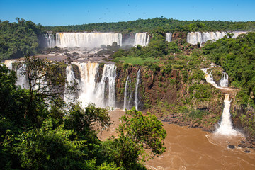 View of spectacular Iguazu Falls with San Martin Island, Salto Tres Mosqueteros (Three Musketeers) and Salto Rivadavia in sunshine, Argentina