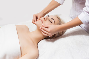 Concept of therapeutic anti-aging skin tightening facial treatments. Close-up hands of an unidentified young woman masseur doing facial massage to beautiful young caucasian client woman at spa salon.