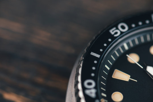 Close up of black diver watch dial. Rustic wooden background. Bezel with marks. Copy space. Top view. Commercial concept.
