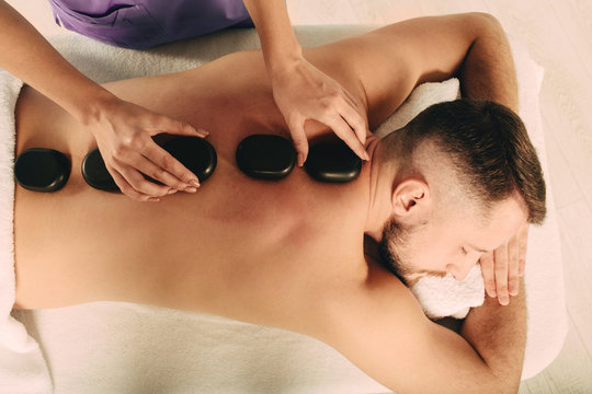 Handsome man at spa resort receive hot stone massage. Speciality massage using smooth, heated stones