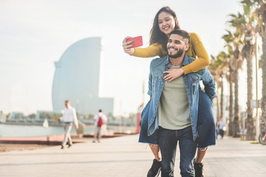 Latin couple taking photos and making videos for social network app in Barcelona - Young people having fun with new technology trends - Travel, tech and millennial concept - Main focus on man face