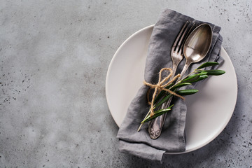 Rustic vintage set of cutlery. Plate with grey linen napkin, fork and spoon, olive tree branch over...