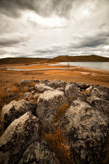 Autumn landscape in the Mongolian steppe. Beautiful river turn among the steppe, aerial view. Colorful and harsh autumn.