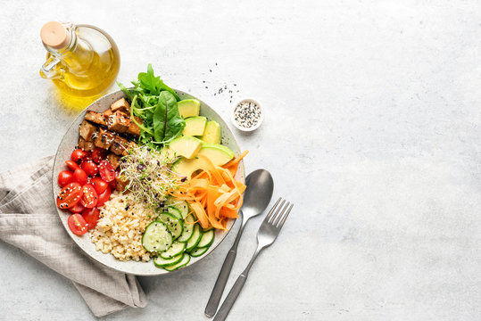 Vegetarian Vegan salad bowl or buddha bowl with grains, tofu, avocado, vegetables and greens. Balanced meal on grey concrete background. Top view, copy space