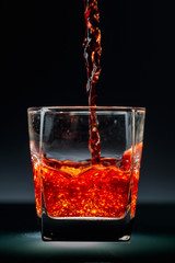 Pouring whiskey or scotch  into glass.