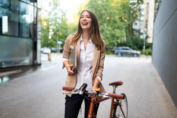 Fototapeta Business woman with bicycle to work on urban street in city. Transport and healthy lifestyle concept obraz