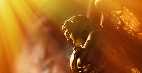 Wall Mural - Gold angel in the sunlight. Antique statue.