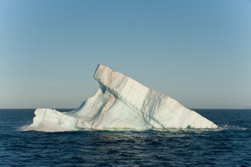 A large iceberg drifts at sea in Arctic Ocean having detached from a glacier.Copy Space above.Climate Crisis.Image.